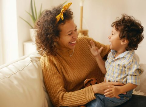 Indoor shot of happy young Hispanic woman with brown wavy hair relaxing at home embracing her adorable toddler son. Cheerful mother bonding with infant son, sitting on sofa in living room, laughing