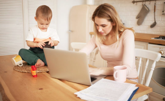 Worried upset young blonde female sitting at kitchen table with papers and portable computer feeling stressed because she has to make report and take care of her baby son while he is staying at home