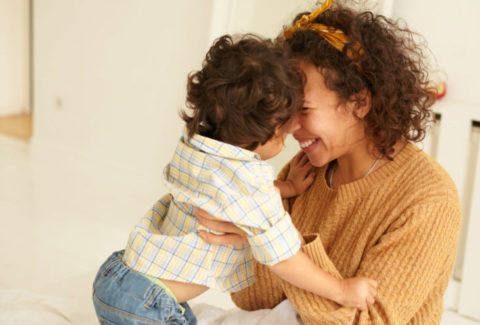 Cozy scene of happy overjoyed young curly haired mother cuddling baby son in her arms, bonding in bedroom, enjoying motherhood, feeling deep conection to her infant child. Love and happiness